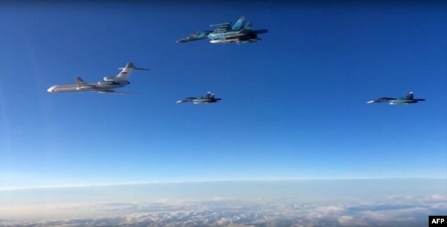 A video grab made on March 15, 2016, shows an image taken from a footage made available on the Russian Defence Ministry's official website on March 15, 2016, reportedly showing Russian Su-34 bombers and a Tupolev Tu-154 transport plane (L) flying above an unknown location on their way from the Hmeimim airbase in Syria to their permanent bases in the Russian Federation.