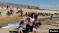 میکسکو - امریکہ کی سرحد پر اکھٹے ہونے والے تارکین وطن اشک آور گیس سے بچنے کے لیے بھاگ رہے ہیں۔ 25 نومبر 2018