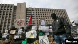 Người biểu tình thân Nga đeo mặt nạ đứng canh gác cạnh các chướng ngại vật bên ngoài một tòa nhà chính phủ trong khu vực Donetsk, miền đông Ukraine.