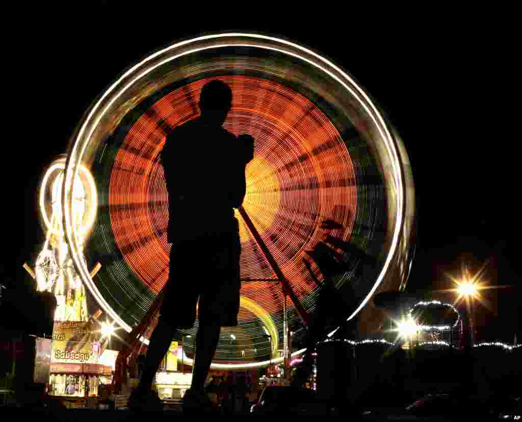 A fairgoer is silhouetted while watching the Ferris wheel at the Iowa State Fair in Des Moines, Aug. 16, 2015.