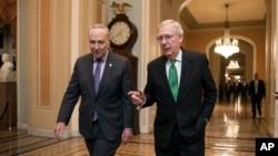 美国参议院多数党领袖麦康奈尔(右)和参议院少数党领袖查克·舒默(D-New York)2018年2月7日在华盛顿的国会大厦就预算协议合作后走进会议厅。