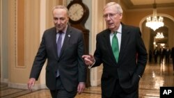 Senate Majority Leader Mitch McConnell, R-Ky., and Senate Minority Leader Chuck Schumer, D-N.Y., left, walk to the chamber after collaborating on an agreement on a two-year, nearly $400 billion budget deal.