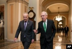 Senate Majority Leader Mitch McConnell, R-Ky., and Senate Minority Leader Chuck Schumer, D-N.Y., left, walk to the chamber after collaborating on an agreement on a two-year, nearly $400 billion budget, Feb. 7, 2018.