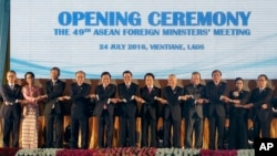 FILE- In this June 24, 2016, file photo, Laotian Prime Minister Thongloun Sisoulith, sixth from left, and Laotian Foreign Minister Saleumxay Kommasith, sixth from right, join their hands with Southeast Asian foreign ministers, from left, an unidentified d