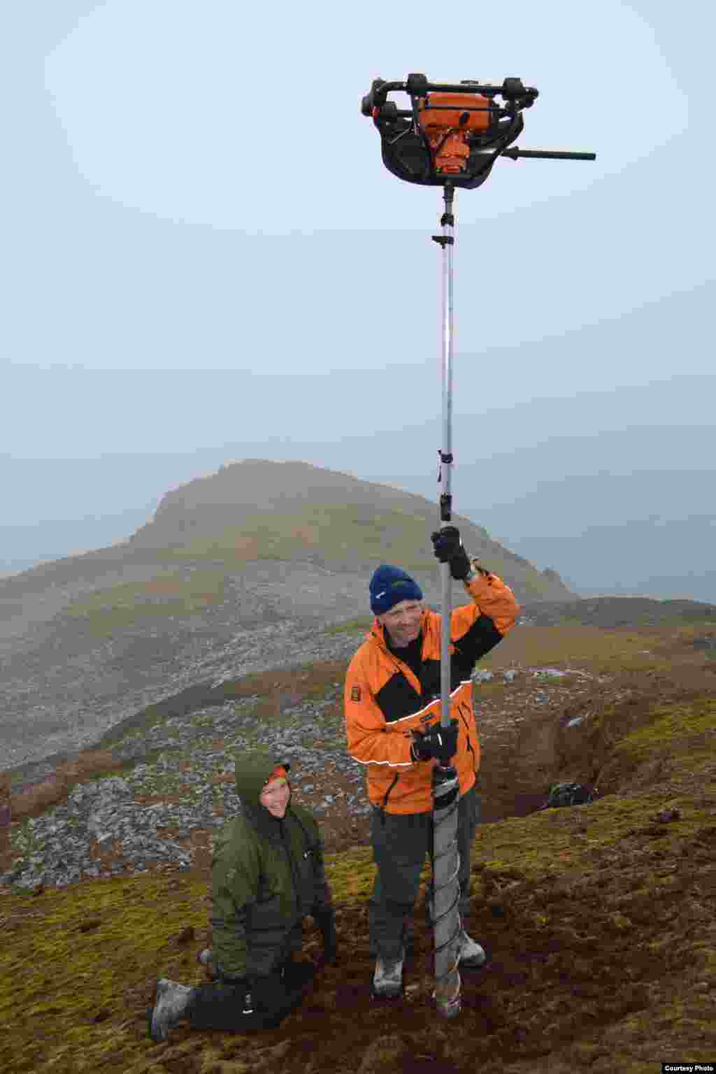 British Antarctic Survey scientists Dominic Hodson and Jessica Royles work with core sampling equipment on a high elevation moss bank on Elephant Island, South Shetland Islands. (Dan Charman/Matt Amesbury)