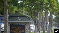Sebuah tanda di pintu masuk kota mengingatkan penduduk untuk mengeringkan atau menutup air yang tidak mengalir untuk mencegah nyamuk berkembang biak. Key Biscayne, Florida. (AP Photo/Wilfredo Lee)