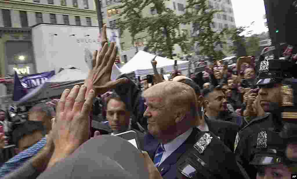 In this image made from video, Republican presidential candidate Donald Trump greets supporters outside his Trump Tower building in New York on Saturday.