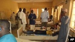 Para korban ledakan bom bunuh diri pada sebuah tempat menonton Piala Dunia menerima perawatan di rumah sakit di Damaturu, Nigeria (18/6). (AP/Adamu Adamu)