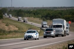 A Russian aid convoy of trucks is escorted by a police vehicle as they travel on a road to the border control point in the Russian town of Donetsk, in the Rostov-on-Don region, Russia, Aug. 17, 2014.