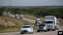 A Russian convoy of trucks carrying humanitarian aid for Ukraine is escorted by a police vehicle as they travel on a road to the border control point in the Russian town of Donetsk, in the Rostov-on-Don region, Russia, Aug. 17, 2014.