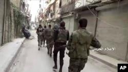 ກອງກຳລັງລັດຖະບານ ຍ່າງລາດຕະເວນ ຢູ່ໃນຊຸມຊົນ Bustan Al-Basha, ເມືອງ Aleppo, ຊີເຣຍ.