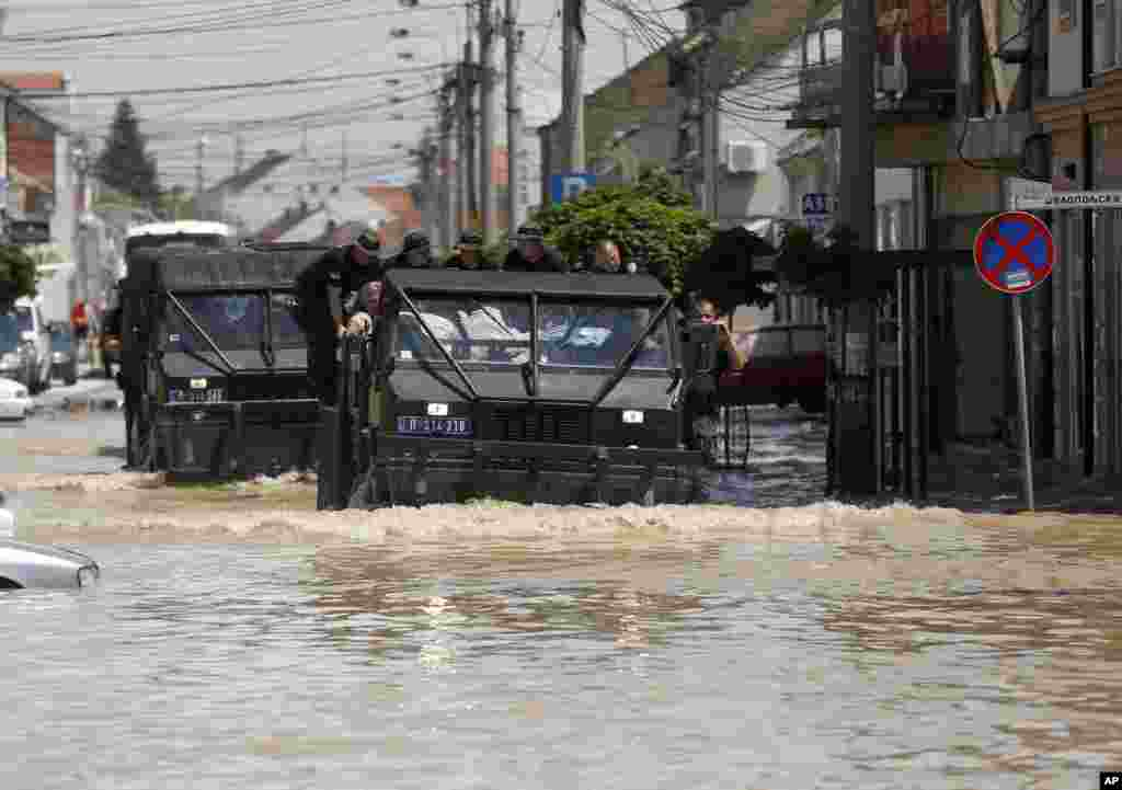 Police vehicles drive through a flooded street in Obrenovac, Serbia, May 20, 2014.