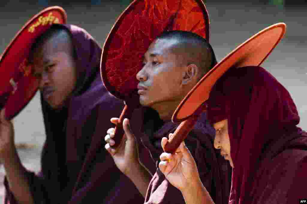 Myanmar Buddhist monks hold fans as sunshades during a protest march by students and Buddhist monks in Letpadan, some 130 kilometers (80 miles) north of Myanmar's main city of Yangon. Students have rallied for months over a controversial education bill that they say is undemocratic.