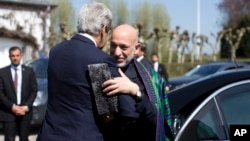 U.S. Secretary of State John Kerry, left, greets Afghan President Hamid Karzai, Brussels, Belgium, April 24, 2013.