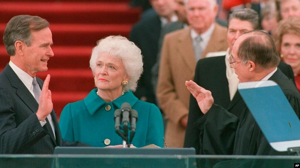 En esta foto del 20 de enero de 1989, George H.W. Bush jura al cargo como presidente número 41 de Estados Unidos ante el presidente de la Corte Suprema, William Rehnquist, mientras la primera dama Barbara Bush sostiene la Biblia.