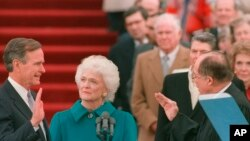 FILE - President George H.W. Bush raises his right hand as he is sworn into office as the 41st president of the United States by Chief Justice William Rehnquist outside the west front of the Capitol as first lady Barbara Bush holds the bible for her husband, Jan. 20, 1989.