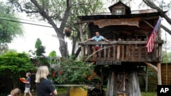 Dr. Jason Barnes, top right, sits in his kids' treehouse while his family plays in their backyard, April 18, 2020, in Corpus Christi, Texas.