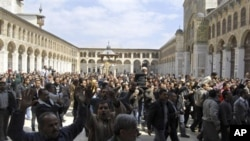 Syrian protesters shout slogans outside the Omayyad Mosque after Friday prayers in Damascus, March 25, 2011