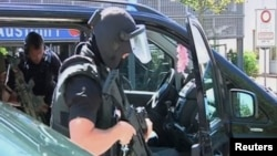 German special police leave their cars in this still image taken from video after a masked man with a gun and ammunition belt opened fire in a cinema complex and took hostages before police killed him, in Viernheim, near Frankfurt, Germany, June 23, 2016.