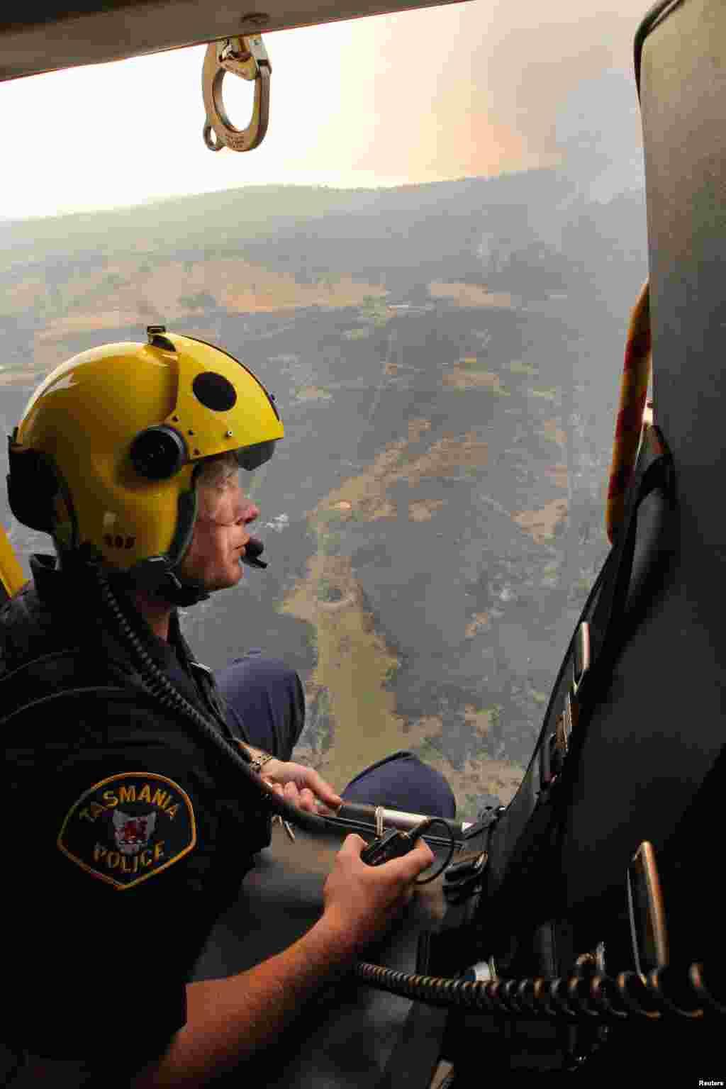 Anggota awak helikopter penyelamatan polisi Matthew Drumm mengamati kebakaran di Dunnalley, sebelah timur Hobart, negara bagian Tasmania (5/1).