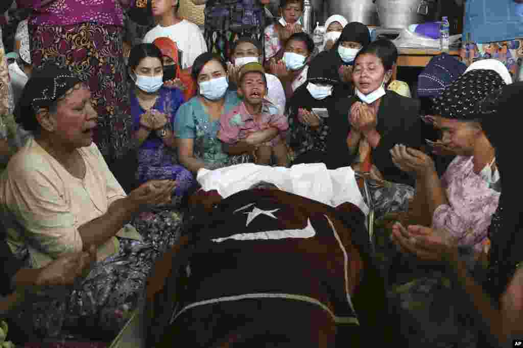 Family and relatives pray next to the body of the Muslim woman who her family said was killed by the army Sunday, during her funeral service in Mandalay, Myanmar.