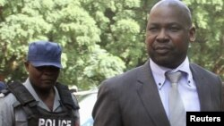 FILE: Zimbabwe's Prosecutor General Johannes Tomana (R) arrives escorted by policemen at the Harare Magistrates court, Feb. 2, 2016.