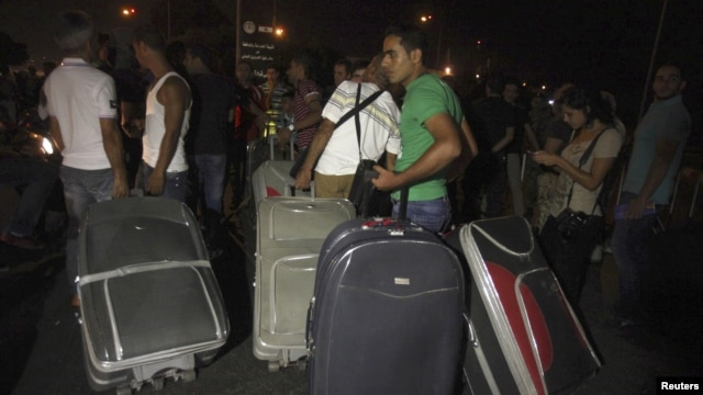Passengers carrying baggage try to pass, after main road leading to Beirut airport was blocked by relatives of the 11 Lebanese Shi'ite pilgrims who were abducted in Syria, August 15, 2012.