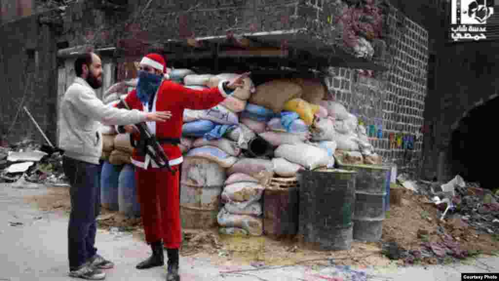 Seorang anggota Tentara Pembebasan Suriah dalam kostum sinterklas menunjukkan arah pada warga Homs di daerah kota tua (1/1). (Lens Young Homsi)