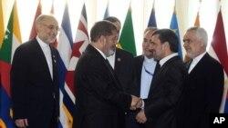 Presiden Iran Mahmoud Ahmadinejad menyambut President Mesir Mohammed Morsi dalam pembukaan KTT Gerakan Non Blok di Teheran (30/8).