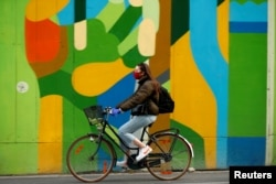 FILE PHOTO: A woman wearing a protective mask rides her bicycle during the coronavirus disease (COVID-19) outbreak, in Brussels, Belgium April 16, 2020. REUTERS/Francois Lenoir/File Photo