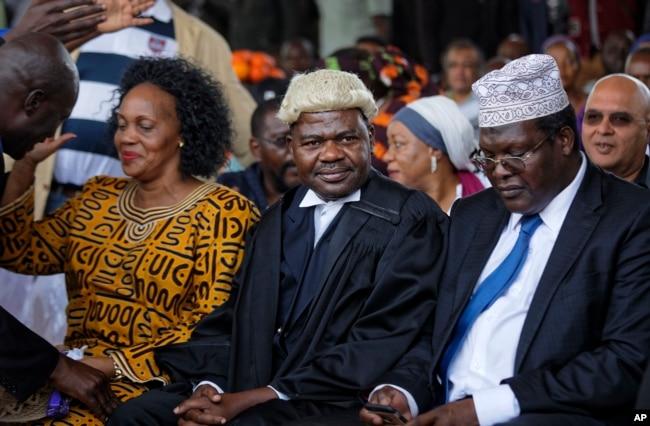 "FILE - Lawyers Miguna Miguna (R), and Tom ""T.J."" Kajwang (C) attend a mock ""swearing-in"" ceremony for opposition leader Raila Odinga at Uhuru Park in downtown Nairobi, Kenya, Jan. 30, 2018."