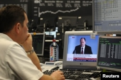 FILE - A share trader watches German Finance Minister Peer Steinbrueck's on an incresing impact of the global financial crisis, on television at the Frankfurt stock exchange, Oct.13, 2008.
