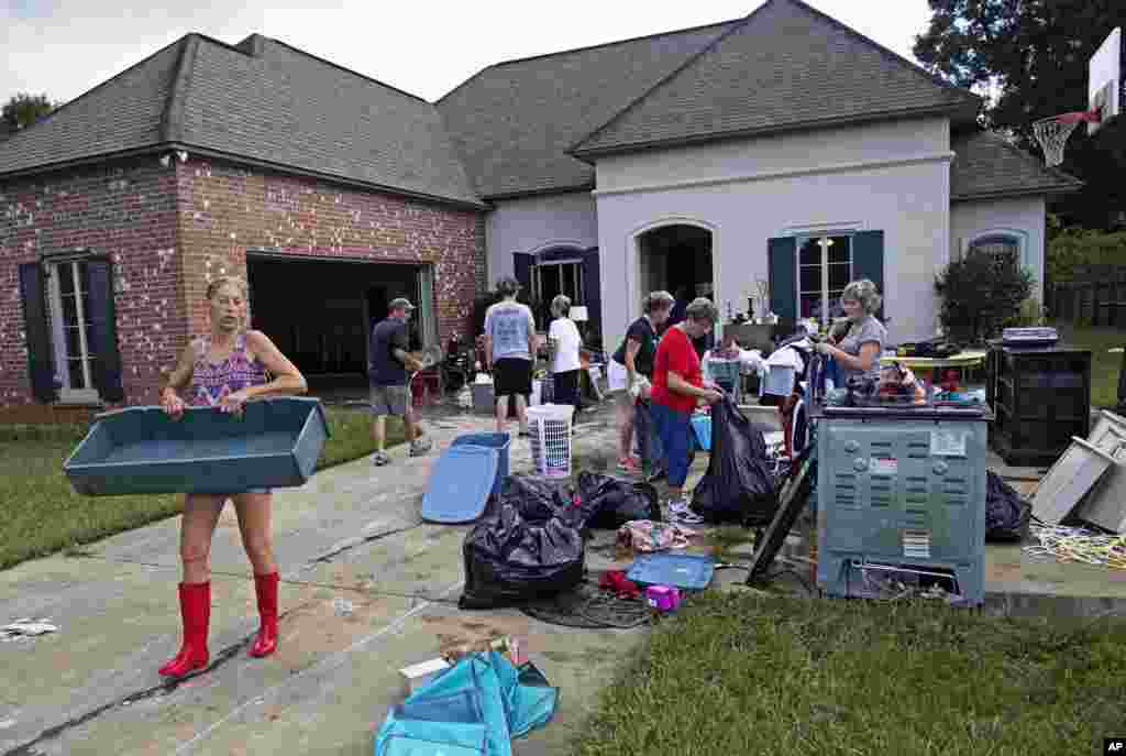 Raven Harelson, 59, left, carries a drawer to the trash heap in front the home of Sheila Siener, 58, as friends and family help to clean out the flood-damaged home in St. Amant, Louisiana, Aug. 20, 2016.
