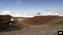 FILE - Observatories sit atop Hawaii's Mauna Kea, near Hilo, Hawaii, Aug. 31, 2015. Hearings are still underway for a permit to build what would be one of the world's largest telescopes in Hawaii, but a group challenging the project is already appealing to the state Supreme Court. Thirty Meter Telescope opponents are challenging various decisions that have been made regarding contested-case proceedings, including affirming the hearings officer and an order limiting cross-examination to 30 minutes per party.