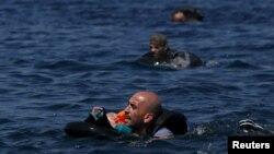 13일 터키에서 고무보트를 타고 그리스 레스보스 섬으로 가려다 물에 빠진 시리아 난민이 구명정 위에 아기를 얹은 채로 해안을 향해 헤엄치고 있다.
