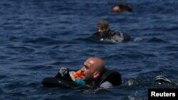 Un refugiado sirio sostiene a su bebé en un salvavidas, mientras nada hacia la costa frente a las isla de Lesbos, en Grecia.