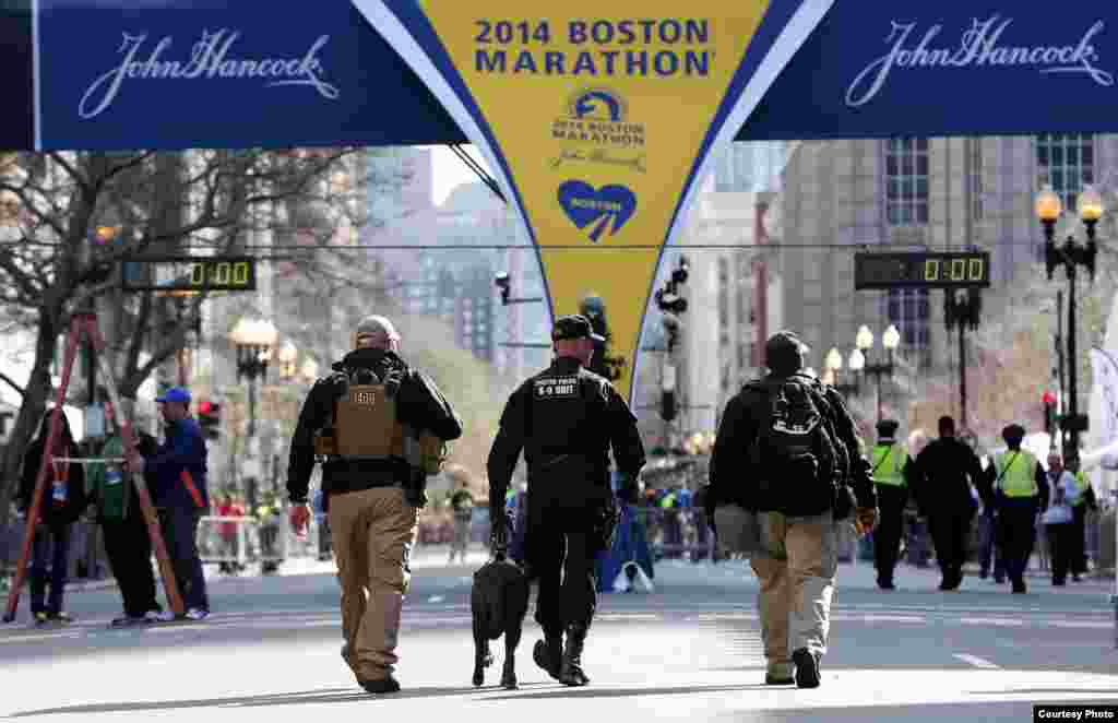 Apr 21, 2014; Boston, MA, USA; Boston police officers part of the K-9 unit patrol Boylston Street near the finish line before the start of the 2014 Boston Marathon. Mandatory Credit: Greg M. Cooper-USA TODAY Sports - RTR3M2SC