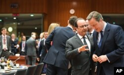 British Prime Minister David Cameron, right, speaks with French President Francois Hollande during a round table meeting at an EU summit in Brussels on Tuesday, June 28, 2016.
