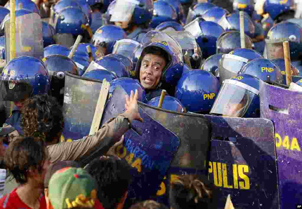Seorang petugas kepolisian berteriak pada rekannya selama terjadinya bentrokan dengan para pengunjuk rasa ketika mereka mencoba untuk memaksa mendekati gerbang Kedubes AS di Manila, Filipina, untuk menandai peringatan Hari Buruh Internasional.