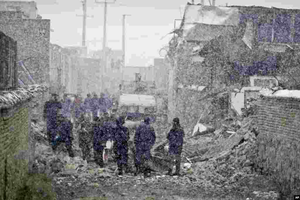 Security personnel inspect the scene of a car bomb explosion in Kabul, Afghanistan, December 17, 2012.