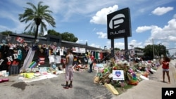 This photo taken July 11, 2016, shows visitors taking photos and leaving items at a makeshift memorial outside the Pulse nightclub, the day before the one month anniversary of a mass shooting, in Orlando, Fla.