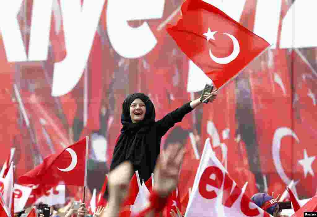 Para pendukung Presiden Turki Recep Tayyip Erdogan melambaikan bendera nasional pada acara kampanye menjelang referendum di kota Konya.