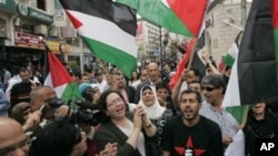 Palestinians wave flags and chant during a rally celebrating the planned signing of a reconciliation agreement between Fatah and Hamas, in the West Bank city of Ramallah, May 4, 2011