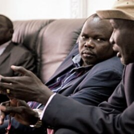 Pagan Amum, Chief Negotiator of the southern Sudan People's Liberation Movement (L), listens to remarks by Stephen Dhieu Dau, Minister of Petroleum and Mining in South Sudan, at Paloich Airport in Melut, South Sudan, February 21, 2012