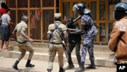 FILE - Ugandan security forces briefly beat then detain a protester in downtown Kampala, Uganda, Aug. 20, 2018. Two women say they were assaulted by Ugandan security officers in an August 13 incident.