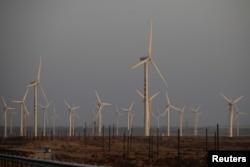FILE - A car drives near wind turbines on a power station near Yumen, Gansu province, China, September 29, 2020.