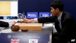 South Korean professional Go player Lee Sedol, right, puts the first stone against Google's artificial intelligence program, AlphaGo, during the Google DeepMind Challenge Match in Seoul, South Korea, March 9, 2016.