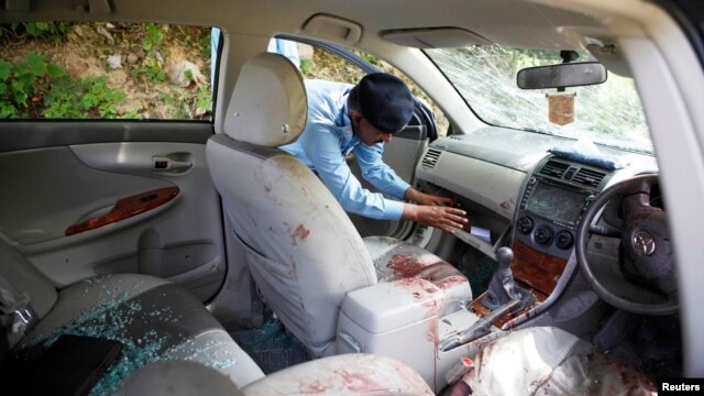 A policeman collects evidence from the car in which prosecutor Chaudhry Zulfikar was traveling, when he came under attack from unidentified gunmen in Islamabad, May 3, 2013.