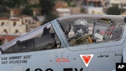 A French pilot gives a thumbs-up before taking off in a Mirage 2000 fighter jet from the Greek air base at Souda on the island of Crete, March 30, 2011