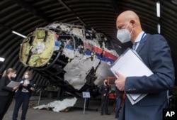 Hakim Ketua Hendrik Steenhuis, kanan, dan hakim pengadilan serta pengacara lainnya melihat puing-puing pesawat Malaysia Airlines MH17 yang direkonstruksi, di pangkalan militer Gilze-Rijen, Belanda selatan, Rabu, 26 Mei 2021. (Foto: AP)